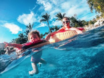 Mother and daughter floating in pool