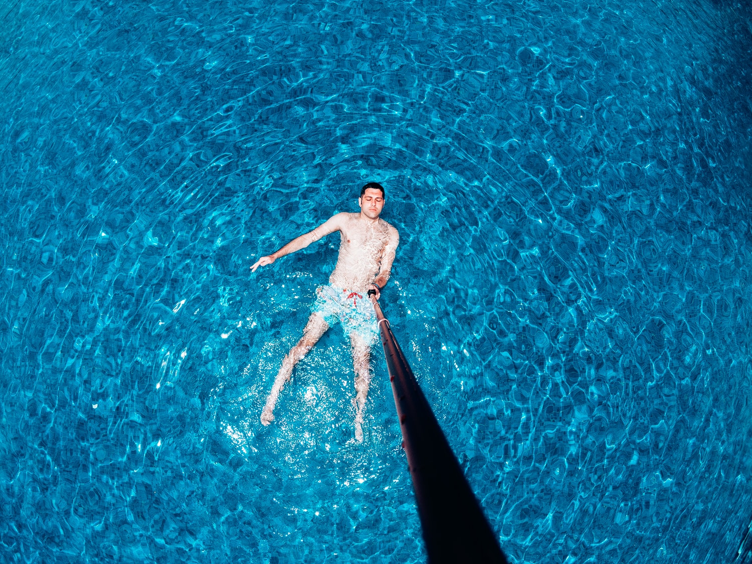 man floating in swimming pool with long selfie stick
